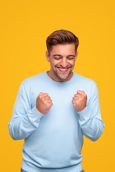 Jeune homme souriant et célébrant le succès