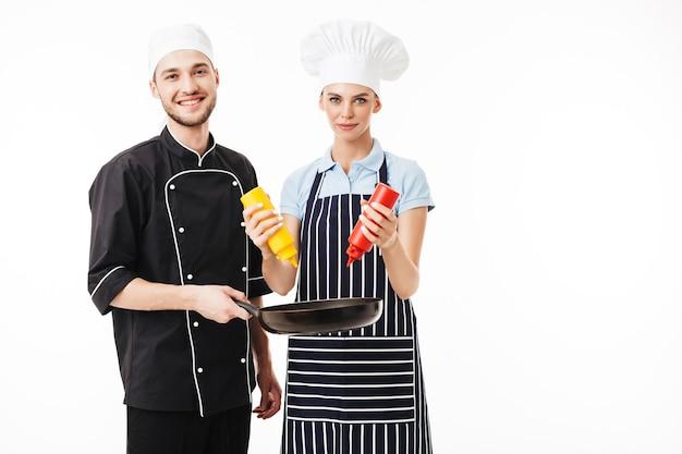 Jeune homme souriant chef en uniforme noir tenant la casserole dans les mains tandis que la femme cuisinier en tablier rayé tenant des bouteilles de ketchup et de moutarde tout en heureusement