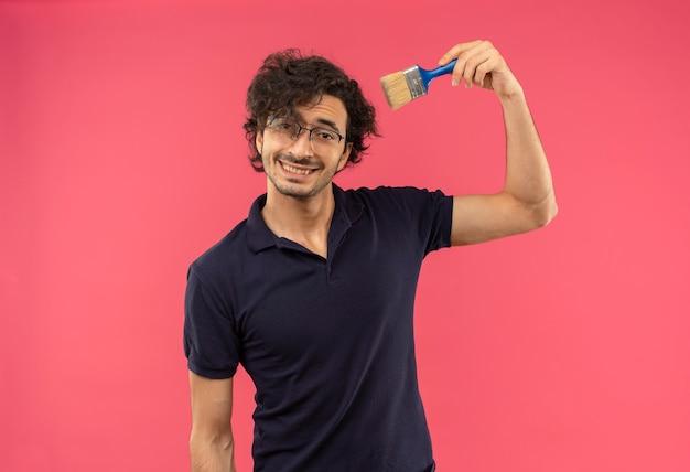Jeune homme souriant en chemise noire avec des lunettes optiques détient un pinceau isolé sur un mur rose