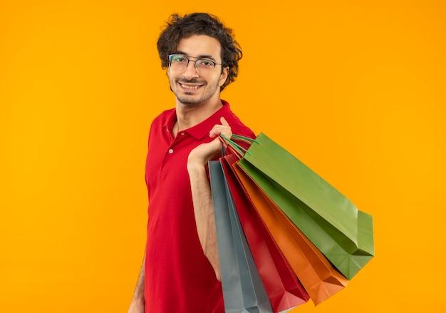 Jeune homme souriant en chemise rouge avec des lunettes optiques détient des sacs en papier multicolores et semble isolé sur mur orange