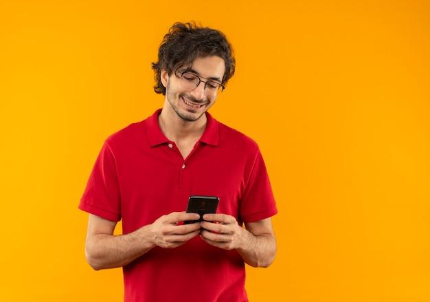 Jeune homme souriant en chemise rouge avec des lunettes optiques tient et regarde le téléphone isolé sur le mur orange