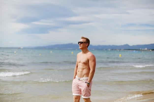 Un jeune homme souriant avec un corps athlétique pose sur la plage près de l'océan en journée d'été. concept de vacances. mode de vie sportif.