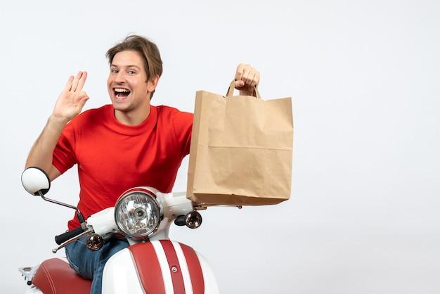 Jeune homme souriant de courrier en uniforme rouge assis sur un scooter tenant un sac en papier et faisant des gestes de lunettes sur un mur jaune