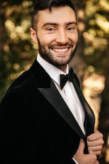 Jeune homme souriant dans un costume noir avec un nœud papillon.