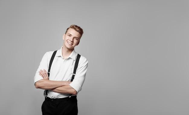 Jeune homme souriant drôle sur mur gris dans un style classique, copy space