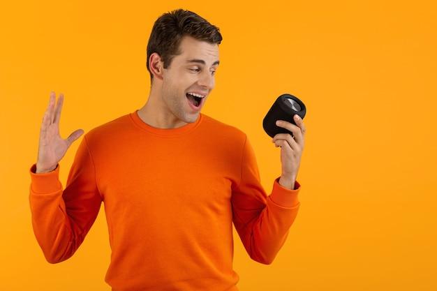 Jeune homme souriant élégant en pull orange tenant un haut-parleur sans fil heureux d'écouter de la musique en s'amusant