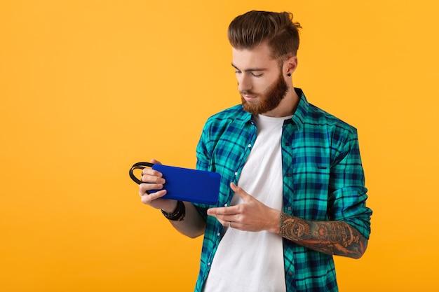 Jeune homme souriant élégant tenant un haut-parleur sans fil écoutant de la musique