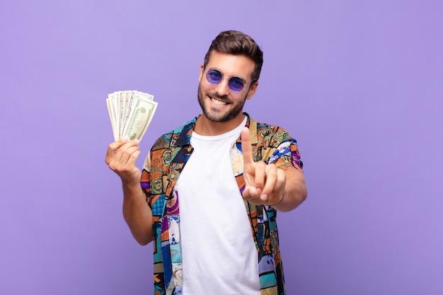 Jeune homme souriant fièrement et en toute confiance faisant la pose numéro un triomphalement, se sentant comme un leader. concept de vacances