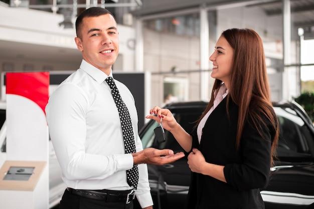 Jeune homme souriant heureux pour sa nouvelle voiture