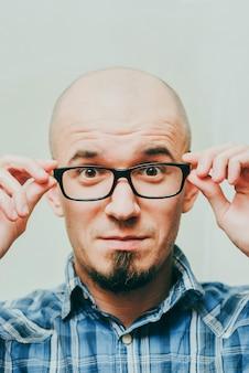 Jeune homme souriant. homme élégant portant des lunettes, regardant la caméra et souriant