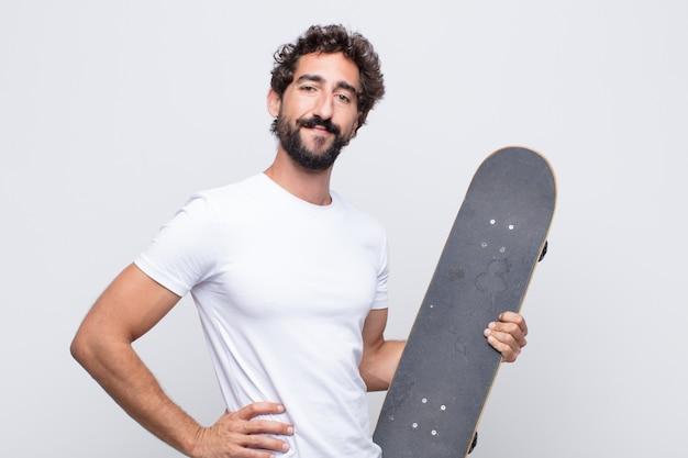 Jeune homme souriant joyeusement avec une main sur la hanche et une attitude confiante, positive, fière et amicale
