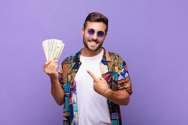 Jeune homme souriant joyeusement, se sentant heureux et pointant vers l'argent