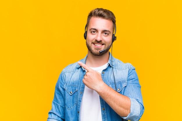 Jeune homme souriant joyeusement, se sentant heureux et pointant vers le côté et vers le haut, montrant l'objet dans l'espace de copie