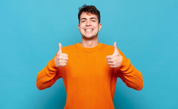 Jeune homme souriant largement à la recherche de bonheur, positif, confiant et réussi, avec les deux pouces vers le haut