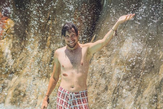 Un jeune homme souriant avec une main levée se tient sous une cascade dans un parc aquatique par une belle journée d'été ensoleillée entourée de nombreuses gouttes scintillantes