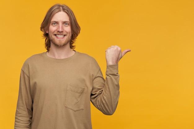 Jeune homme souriant, mec positif aux cheveux blonds, barbe et moustache. porter un pull beige. et pointant le pouce vers la droite à l'espace de copie, isolé sur un mur jaune