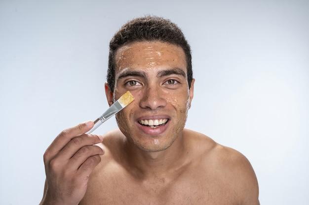 Jeune homme souriant mettant un masque d'humidité
