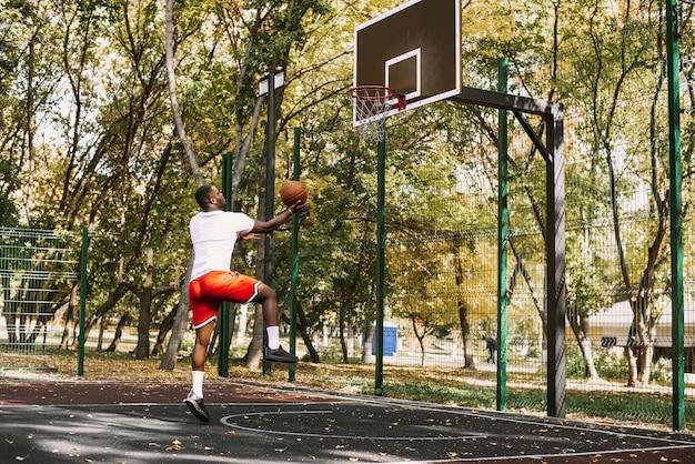 Jeune homme souriant noir jouant au basket-ball sur le terrain au lever du soleil, sports du matin. portrait en plein air.