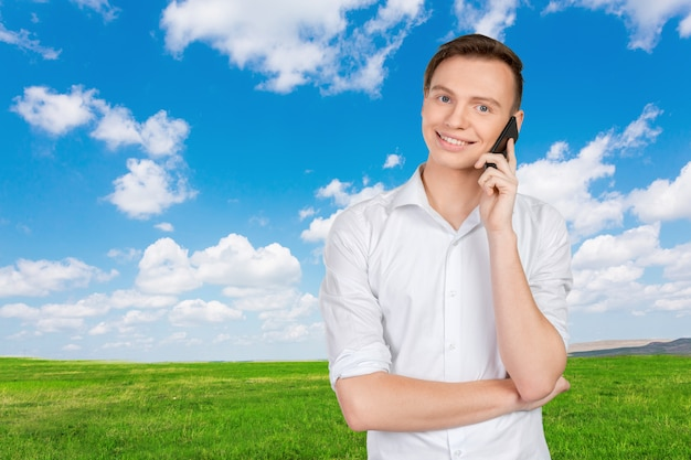 Jeune homme souriant parlant au téléphone