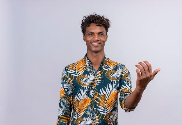 Un jeune homme souriant à la peau sombre avec des cheveux bouclés en chemise imprimée de feuilles et appelant plus près avec le geste de la main