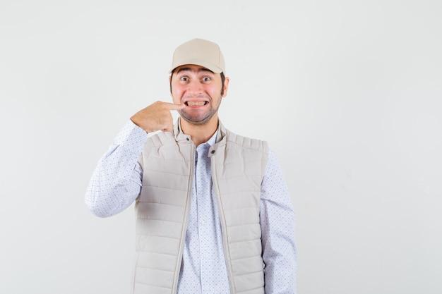 Jeune homme souriant et pointant vers la bouche avec l'index en veste beige et casquette et à la recherche de plaisir. vue de face.