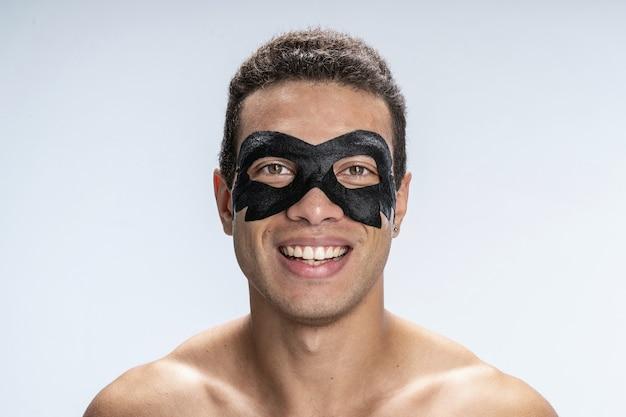 Jeune homme souriant portant un masque facial autour des yeux