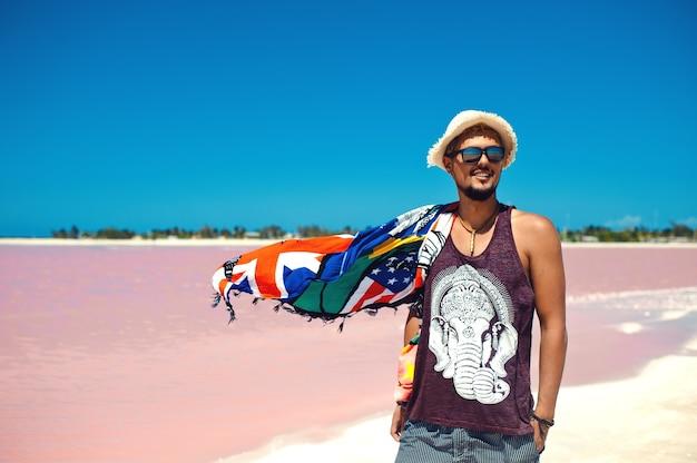 Jeune homme souriant et posant contre le lac salé rose à las coloradas mexique