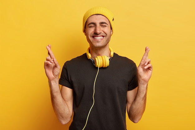Un jeune homme souriant positif prie le rêve devenu réalité, croise les doigts et sourit largement, montre des dents blanches