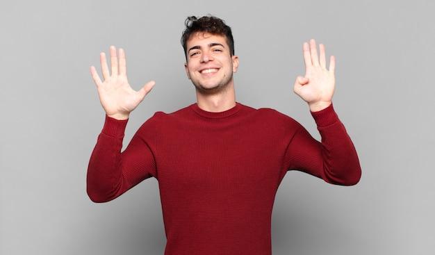 Jeune homme souriant et à la recherche amicale, montrant le numéro neuf ou neuvième avec la main en avant, compte à rebours