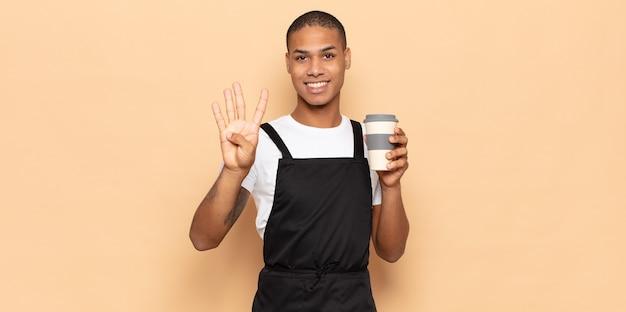 Jeune homme souriant et à la recherche amicale, montrant le numéro quatre ou quatrième avec la main en avant, compte à rebours