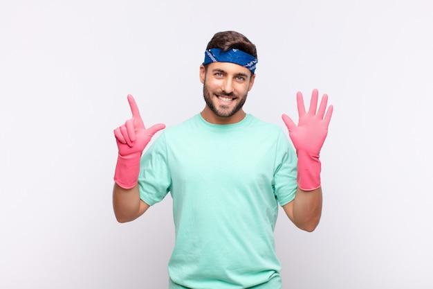Jeune homme souriant et à la recherche amicale, montrant le numéro sept ou septième avec la main en avant, compte à rebours