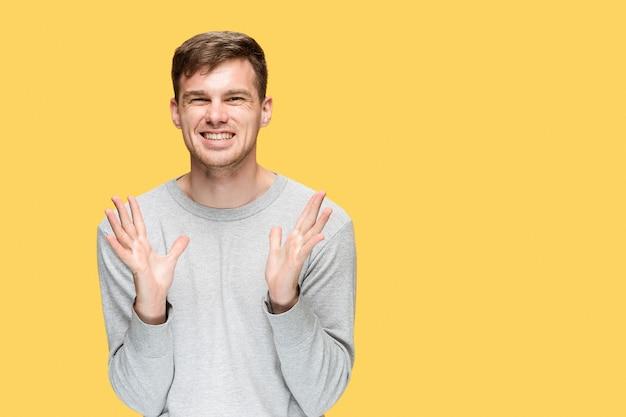 Le jeune homme souriant et regardant la caméra sur fond de studio jaune
