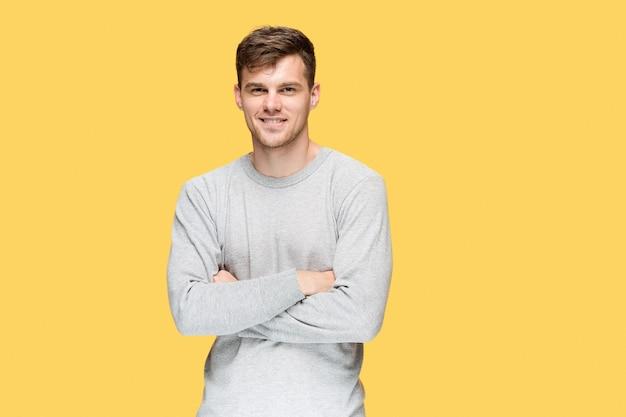 Jeune homme souriant et regardant la caméra sur fond de studio jaune