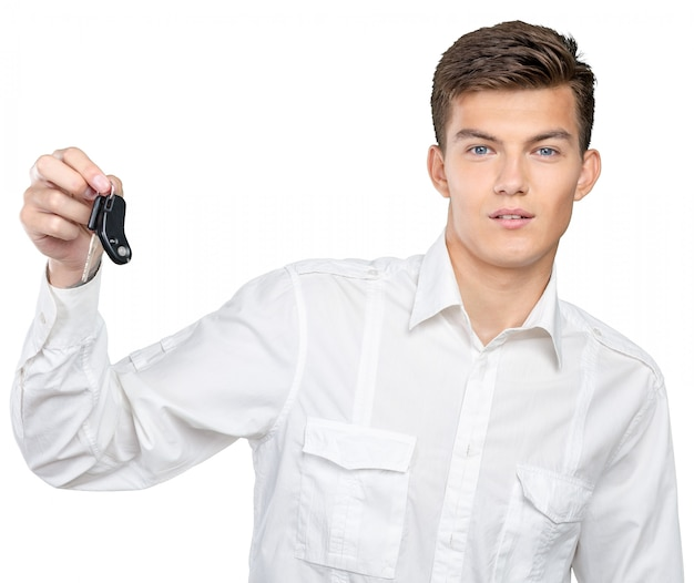 Jeune homme souriant tenant des clefs de voiture