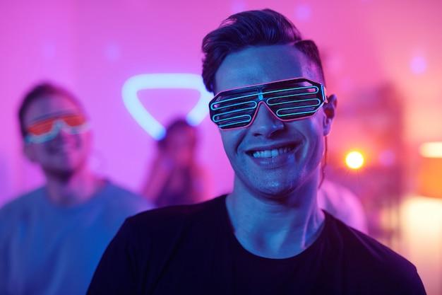 Jeune homme souriant en tenue décontractée et lunettes disco vous regardant tout en se tenant devant ses amis dansant et profitant d'une fête à la maison