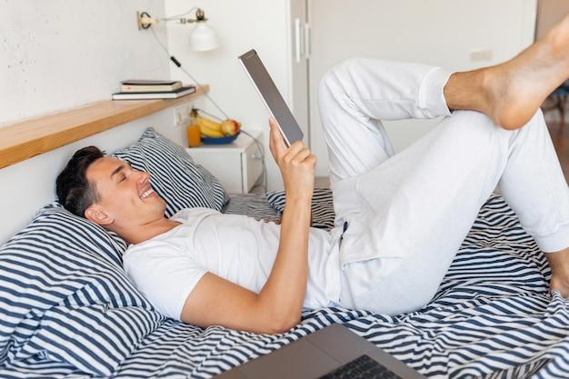 Jeune homme souriant en tenue de pyjama décontracté assis dans son lit le matin tenant la tablette, pigiste à la maison