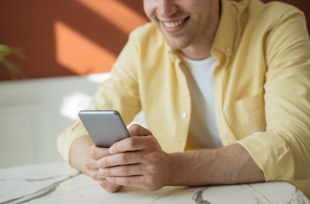 Jeune homme souriant utilisant un téléphone portable faisant des achats en ligne assis dans un café indépendant travaillant à domicile