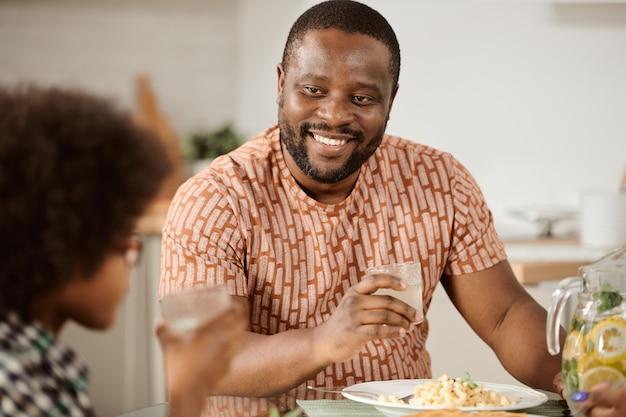 Jeune homme souriant avec un verre de limonade parlant à son petit fils