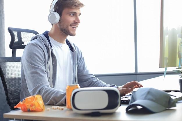 Jeune homme souriant vêtu de vêtements décontractés utilisant un ordinateur, une lecture en continu ou une vidéo pas à pas.