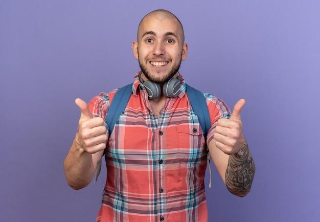 Jeune homme souriant de voyageur avec des écouteurs autour du cou et avec un sac à dos levant isolé sur un mur violet avec espace de copie