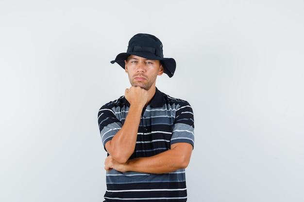 Jeune homme soutenant le menton sur le poing levé en t-shirt, chapeau et semblant sensible, vue de face.