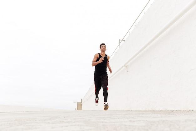 Jeune homme de sport africain qui court à l'extérieur.