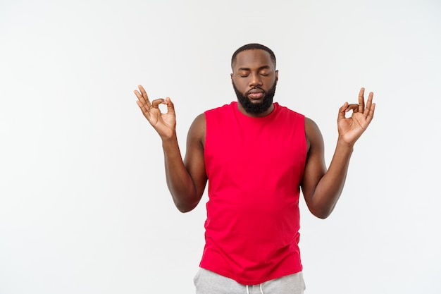 Jeune homme de sport afro-américain méditer isoler sur gris.
