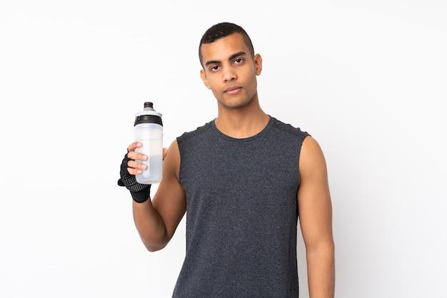 Jeune homme de sport afro-américain sur mur blanc isolé avec bouteille d'eau de sport