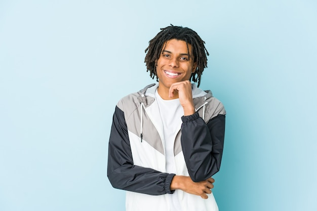 Jeune homme de sport afro-américain souriant heureux et confiant, touchant le menton avec la main.