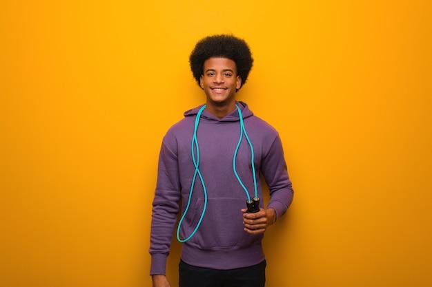 Jeune homme de sport afro-américain tenant une corde à sauter gai avec un grand sourire