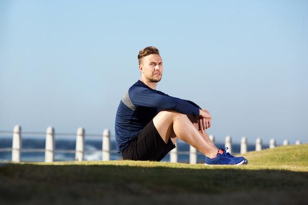 Jeune homme de sport assis dehors après l'entraînement
