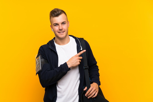 Jeune homme de sport blond isolé sur jaune pointant sur le côté pour présenter un produit