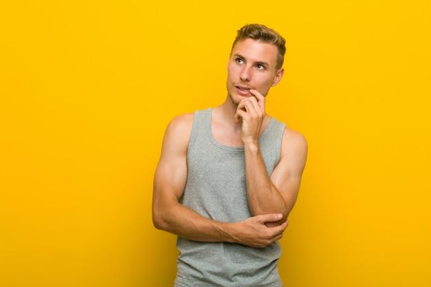Jeune homme de sport caucasien détendu pensant à quelque chose en regardant un espace de copie.