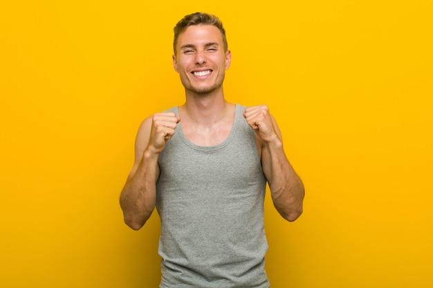 Jeune homme de sport caucasien, levant le poing, se sentant heureux et prospère